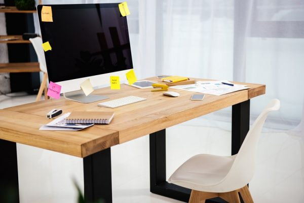 desk and monitor with bright sticky notes