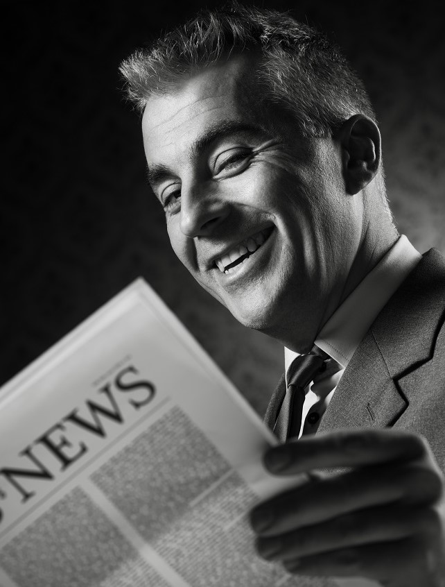 black-and-white photo of a smiling 1950's businessman in a suit reading a newspaper