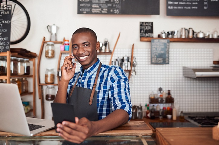 smiling small business male entrepreneur holding a tablet, speaking on the phone in front of his laptop