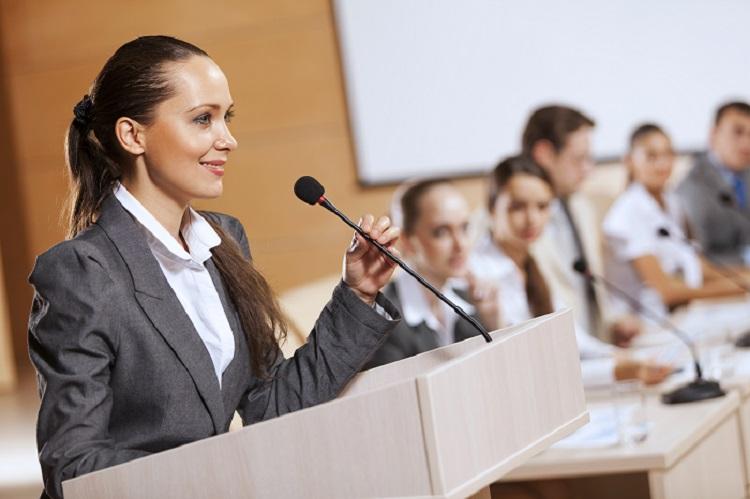 Businesswoman in professional attire speaking onstage