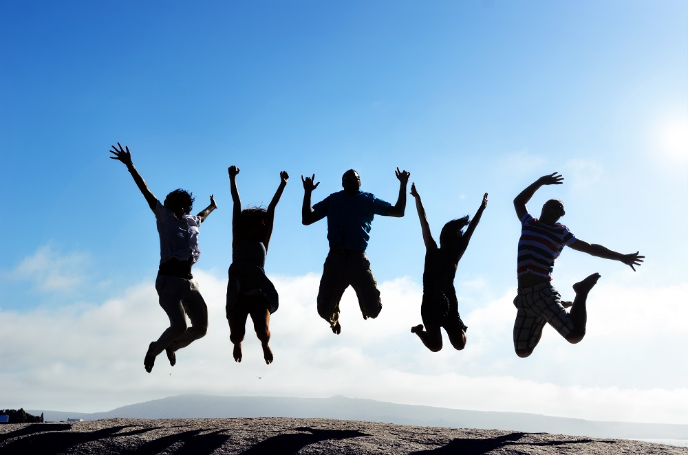 silhouettes of a group of friends jumping for joy outdoors on a beach