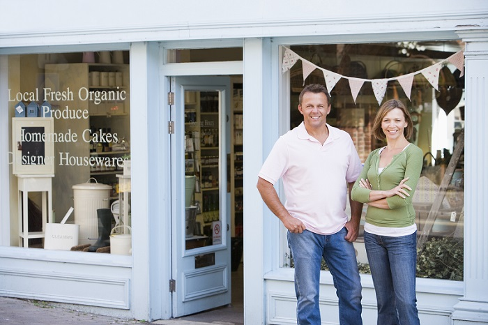 couple standing before storefront of food and housewares specialty store