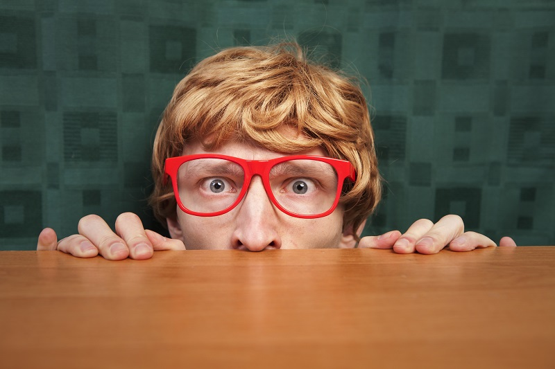 scared red-haired nerdy man with large red glasses peeking from top of a table