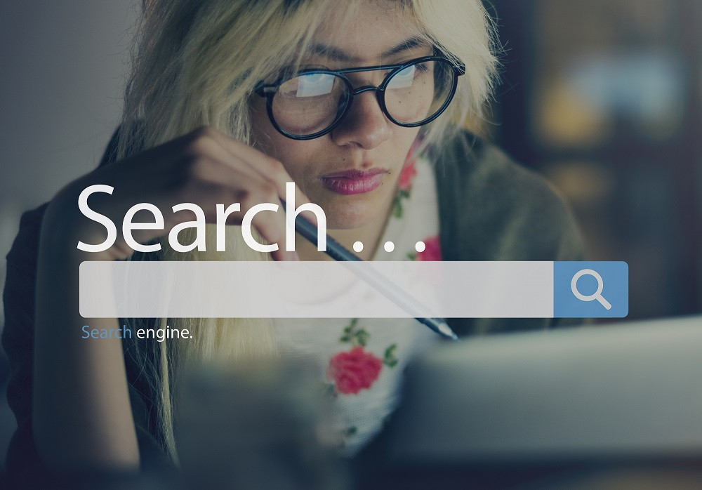 woman peering at computer; google search bar overlays photo