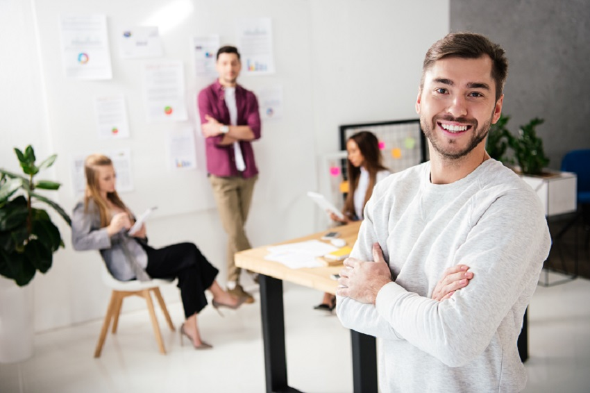 smiling entrepreneur at forefront of meeting with colleagues