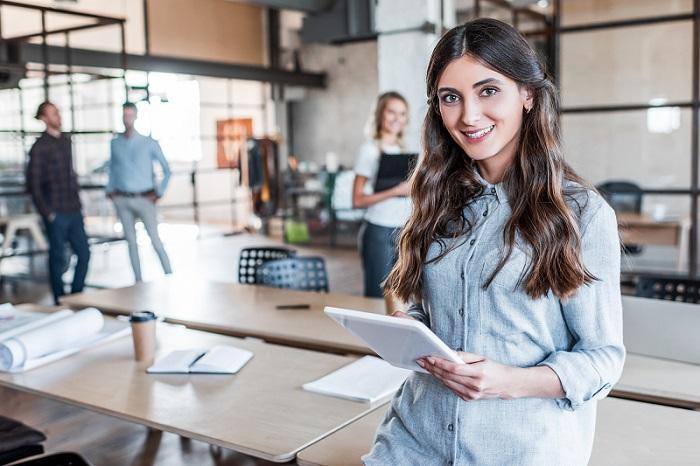smiling businesswoman holding tablet with colleagues in background in modern office