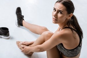female runner on the ground in pain rubbing the bunion on her left foot