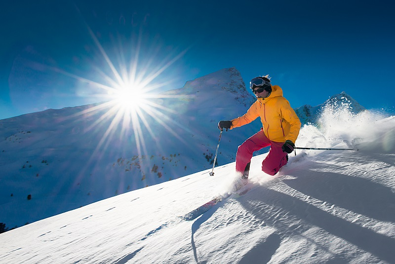 girl skiing happily on beautiful day in fresh powder after successful bunion surgery